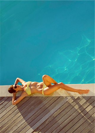 Woman Sunbathing by Swimming Pool, High Angle View Stock Photo - Rights-Managed, Code: 822-07562582