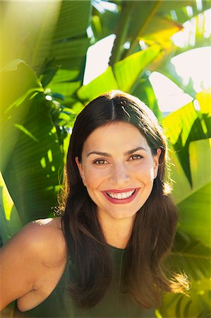 Smiling Woman with Palm Leaves in background Stock Photo - Rights-Managed, Code: 822-07562592