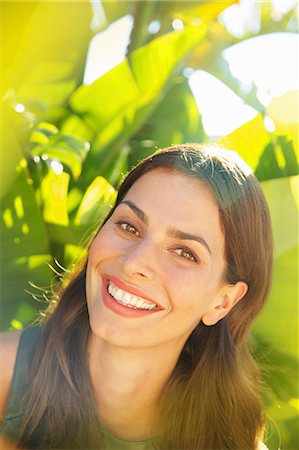 Smiling Woman with Palm Leaves in background Stock Photo - Rights-Managed, Code: 822-07562593