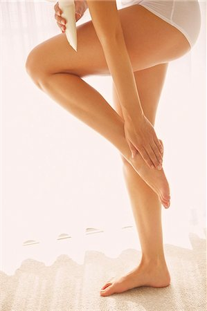 personal care - Woman Applying Body Lotion on Foot, Low Section Stock Photo - Rights-Managed, Code: 822-07562623