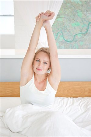 Woman Sitting in Bed Stretching her Arms Stock Photo - Rights-Managed, Code: 822-07562639