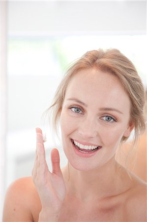 personal care - Smiling Woman with Moisturizing Cream on Hand Stock Photo - Rights-Managed, Code: 822-07562658