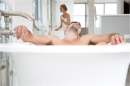 personal care - Man Relaxing in Bathtub, Woman in Background Stock Photo - Rights-Managed, Code: 822-07562662