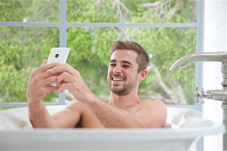 personal care - Smiling Man in Bathtub Taking Selfie Stock Photo - Rights-Managed, Code: 822-07562678