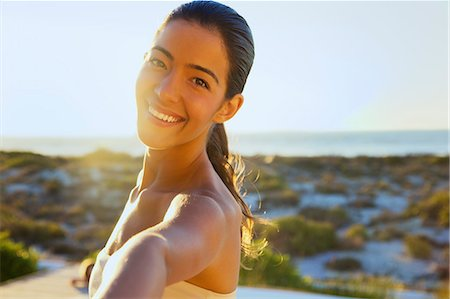 Smiling Young Woman with Arm Raised, Close-up View Stock Photo - Rights-Managed, Code: 822-07562697