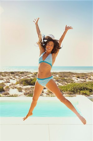 Smiling Young Woman Jumping Mid-air by Swimming Pool Stock Photo - Rights-Managed, Code: 822-07562726