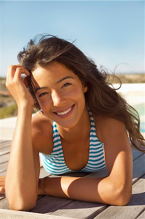 Smiling Young Woman Sunbathing on Deck Stock Photo - Rights-Managed, Code: 822-07562721