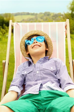 preteen boys playing - Smiling Boy Wearing Straw Hat and Sunglasses Sitting on Deck Chair Stock Photo - Rights-Managed, Code: 822-07708444