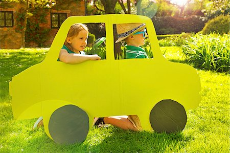Boy and Girl Kneeling behind Cardboard Cut Out in Shape of Car Stock Photo - Rights-Managed, Code: 822-07708442
