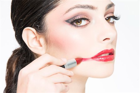 Woman Smearing Red Lipstick on Face, Close-up View Stock Photo - Rights-Managed, Code: 822-07708563
