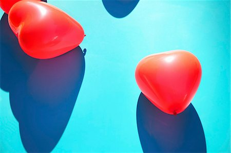 red - Red Heart Shaped Party Balloons on Blue Background Stock Photo - Rights-Managed, Code: 822-07708669