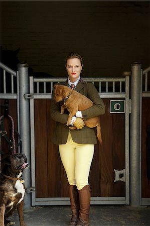 equestrian - Woman in Riding Outfit Standing in front of Stable Carrying Dog in her Arms Stock Photo - Rights-Managed, Code: 822-07840870
