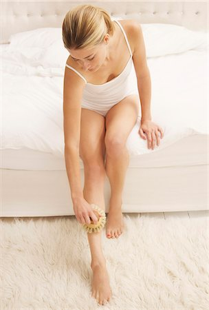 personal care - Woman Sitting on Bed Exfoliating her Leg Stock Photo - Rights-Managed, Code: 822-07840947