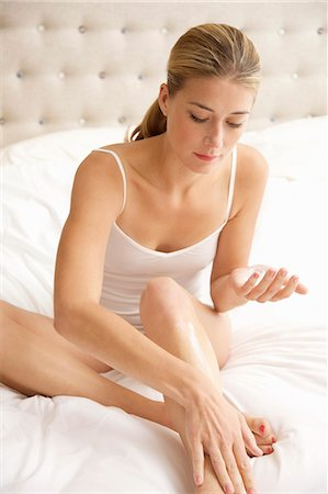 personal care - Woman Sitting on Bed Applying Body Lotion on her Leg Stock Photo - Rights-Managed, Code: 822-07840952