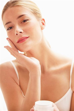personal care - Woman Applying Moisturizing Cream On Face Stock Photo - Rights-Managed, Code: 822-07840953