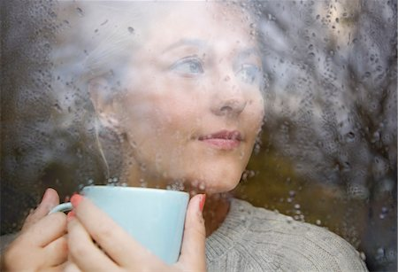 Woman Holding Drinking Cup behind Rainy Window Stock Photo - Rights-Managed, Code: 822-08026256