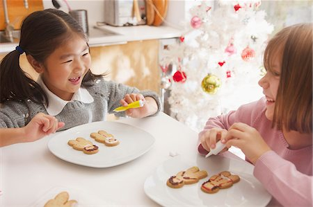 sit - Two Young Girls Decorating Ginger bread man Biscuits Stock Photo - Rights-Managed, Code: 822-08122623