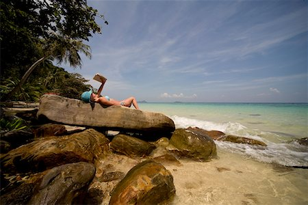 Back of young woman lying on rocks sunbathing and relaxing Stock Photo - Rights-Managed, Code: 822-02124718