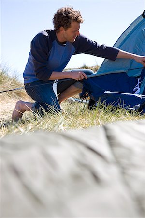 Portrait of young man crouching and erecting tent Stock Photo - Rights-Managed, Code: 822-02136703