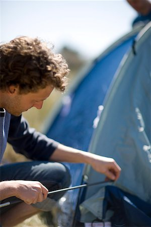 Close up of young man inserting tent pole into tent Stock Photo - Rights-Managed, Code: 822-02137374