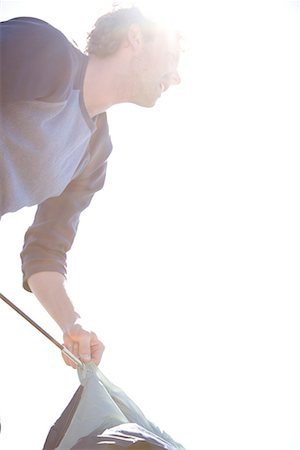 Portrait of young man inserting tent pole into tent Stock Photo - Rights-Managed, Code: 822-02137376