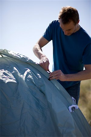 Portrait of young man standing and erecting tent Stock Photo - Rights-Managed, Code: 822-02137377