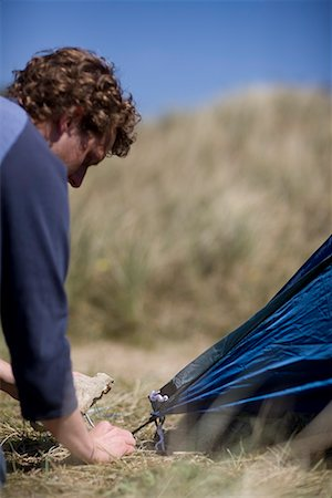Close up of young man fixing tent peg Stock Photo - Rights-Managed, Code: 822-02137379