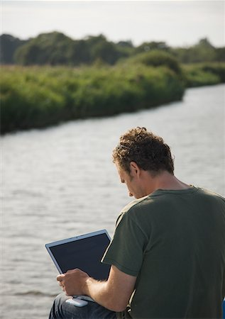 Back view of a man sitting by a river using a laptop computer Stock Photo - Rights-Managed, Code: 822-02315686
