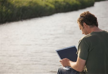 Back view of a man sitting by a river using a laptop computer Stock Photo - Rights-Managed, Code: 822-02315687