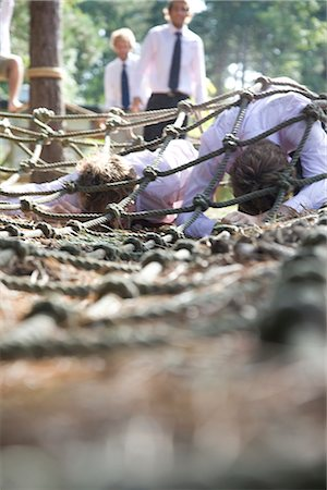 Businessmen at an obstacle course crawling under cargo net Stock Photo - Rights-Managed, Code: 822-02620806