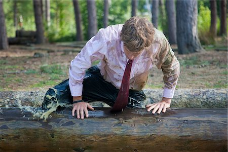Businessman at obstacle course clambering over a wooden beam soaked in muddy water Stock Photo - Rights-Managed, Code: 822-02620816