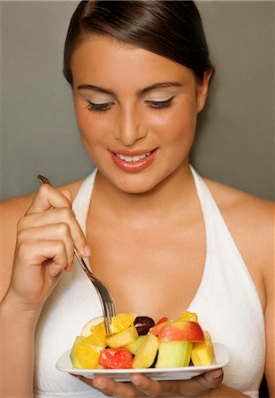 Smiling young woman eating a fruit salad Stock Photo - Rights-Managed, Code: 822-02620935