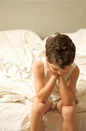 Young boy sitting on the end of a bed with face resting on hands Stock Photo - Rights-Managed, Code: 822-02621189