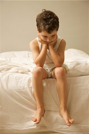 Young boy sitting on the end of a bed with face resting on hands Stock Photo - Rights-Managed, Code: 822-02621190