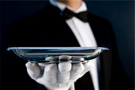 Close up of a waiter wearing white gloves holding a  silver tray in his hand - headless Stock Photo - Rights-Managed, Code: 822-02621271