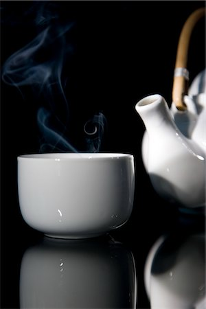 Close up of a steaming green tea teacup and detail of a teapot with wooden handle Stock Photo - Rights-Managed, Code: 822-02621289