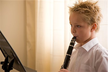 Boy standing in front of a music stand playing the clarinet Stock Photo - Rights-Managed, Code: 822-02621501