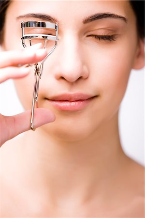 Close up of a young woman using an eylash curler Stock Photo - Rights-Managed, Code: 822-02739314