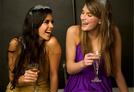 Two girls laughing sitting on the edge of a baththub with  foam in their hair holding glasses of champagne Stock Photo - Rights-Managed, Code: 822-02739400