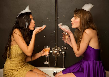 Two girls sitting on the edge of a baththub holding glasses of champagne blowing foam at each other Stock Photo - Rights-Managed, Code: 822-02739451