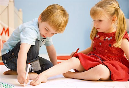 Boy drawing the outline of a girl foot Stock Photo - Rights-Managed, Code: 822-02958174