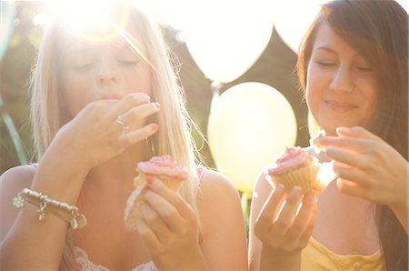 Close up of two smiling teenaged girls at birthday party eating cupcakes Stock Photo - Rights-Managed, Code: 822-03161738
