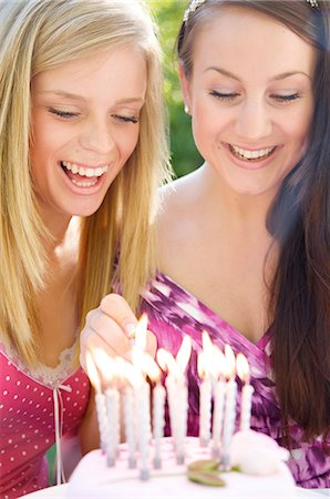 Close up of two teenaged girls lighting candles on a birthday cake Stock Photo - Rights-Managed, Code: 822-03161756