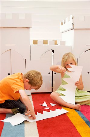 Boy and girl sitting in front of a cardboard castle cutting paper Stock Photo - Rights-Managed, Code: 822-03161777