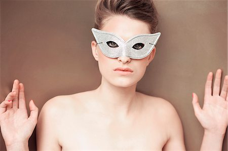 Young woman wearing a party mask with hands up against wall Stock Photo - Rights-Managed, Code: 822-03161805