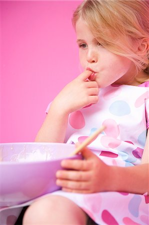 sucking - Close up of a young girl holding a baking bowl sucking her finger Stock Photo - Rights-Managed, Code: 822-03161836