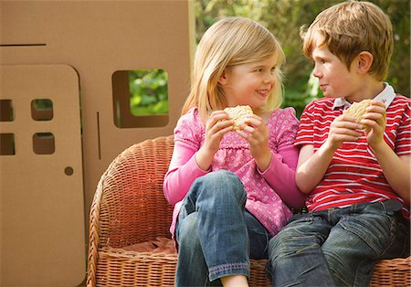 Boy and girl eating biscuits looking at each other Stock Photo - Rights-Managed, Code: 822-03161892