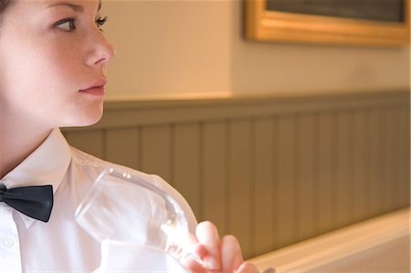 Close up of a waitress holding a wine glass looking to one side Stock Photo - Rights-Managed, Code: 822-03161987