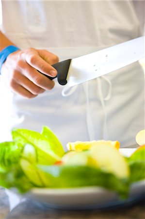 Chef's hand holding a knife standing behind a plate of salad Stock Photo - Rights-Managed, Code: 822-03162136
