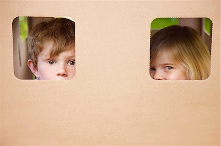 Close up of a boy and girl peeking from the windows of a cardboard playhouse Stock Photo - Rights-Managed, Code: 822-03162154